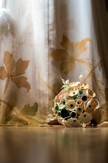 matrimonio sostenibile: bouquet di fiori di carta tinte pastello e abito da sposa dipinto