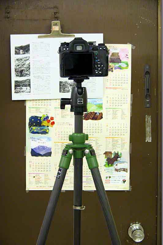 Camera on tripod, aimed at document on door
