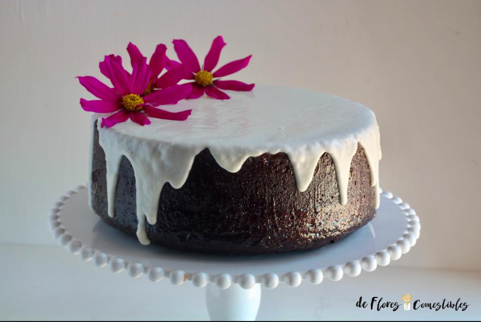 Intenso bizcocho de chocolate sin huevos con glaseado blanco de vainilla y flores