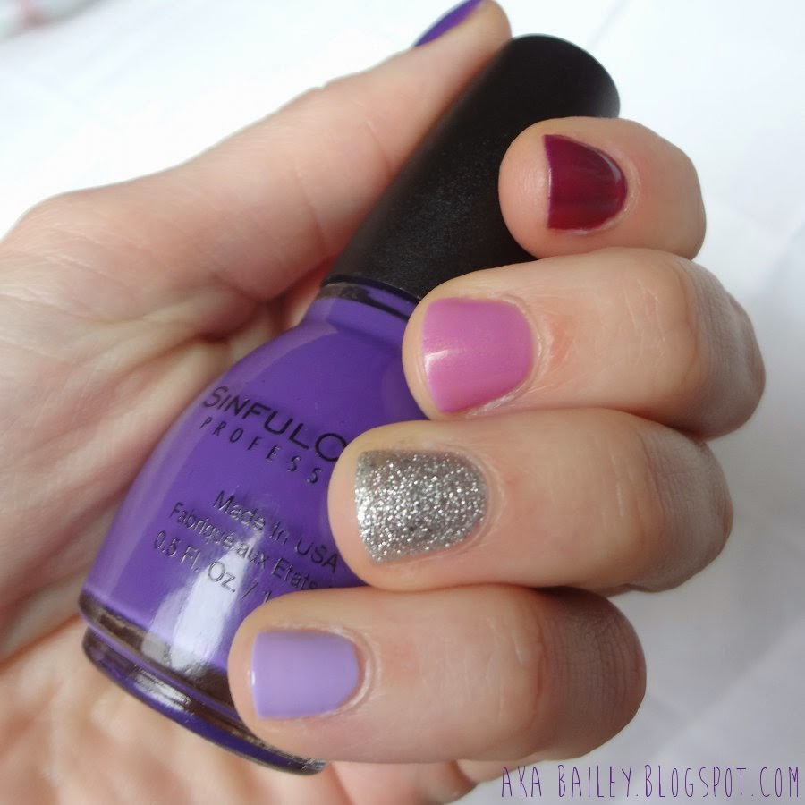 Different purples hues of nail polish, silver glitter accent nail