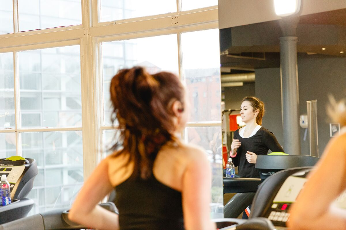 Running on a treadmill, reflection in the gym mirror