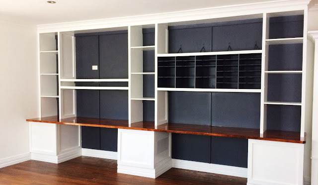 large wall of built ins with desk