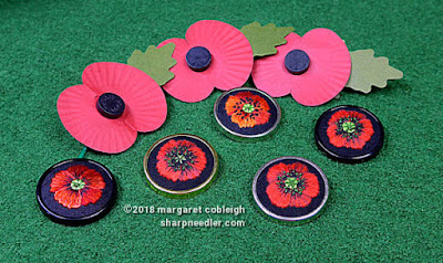 All five embroidered poppies shown with three paper remembrance poppies on green background