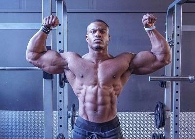 Hombre muy musculado sin camiseta posando en el gimnasio