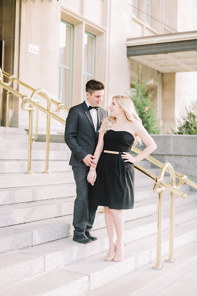 Romantic photoshoot in front of the Fort Gary Hotel, Winnipeg.  Couples outfit idea: classic little black dress and charcoal grey suit.