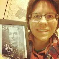 Buchbloggerin neben der Kindle-Version des Buchs, das Cover zeigt Q
