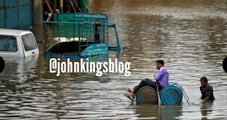 A man is seen using a makeshift raft to move out of a flooded neighborhood after heavy rains in Ahmedabad