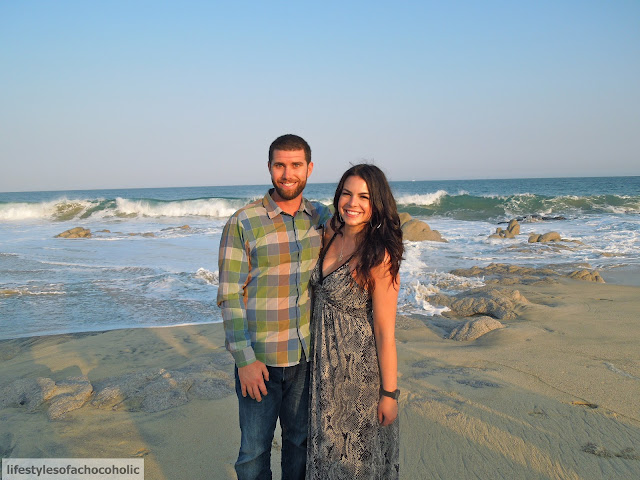 couple standing for a photo on the beach next to waves