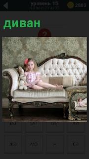 Девочка с большим бантом сидит на мягком диване с мягкой игрушкой зайца