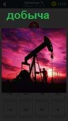 Станок качалка для добычи из скважины нефти в свете заката и управляющий персонал рядом