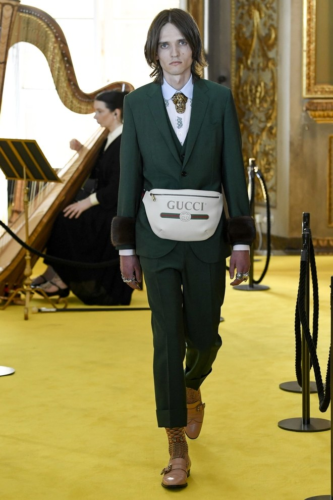 A fanny pack over a suit as an high-fashion item at the Gucci Resort 2018