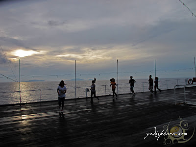 People jogging at the ship poof deck against rising sun