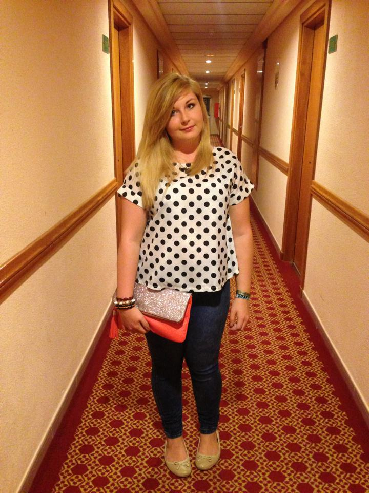 Myself wearing a black and white polka dot t-shirt blouse, with plain blue skinny jeans, a pair of glittery cream dolly shoes, and an orange clutch bag with a glittery flap.