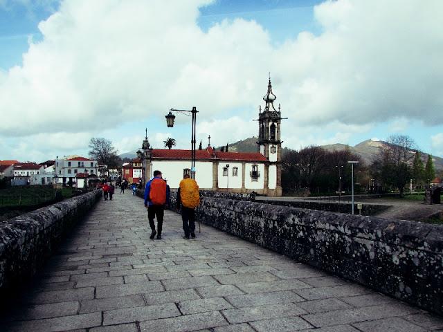 Dois peregrinos de Santiago atravessando a ponte de Ponte de Lima