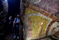 "People walk towards the restored ""dei Fornai"" (bakers) cubicle, during a visit after the restoration of the catacomb of Santa Domitilla, in central Rome, on May 30, 2017 [Credit: AFP/Andreas Solaro]"