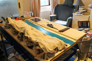 Another photograph of a hilly model set with stream being built on a workshop table.