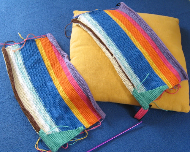 Two matching placemats in progress. The right one is resting on a yellow cushion, the left one is resting on a blue cloth. The right one has a black stitch marker on the top left edge and a bobbin of hot pink cotton on the bottom right edge.  The tip of a purple hook can be seen below the yellow cushion and bobbin.