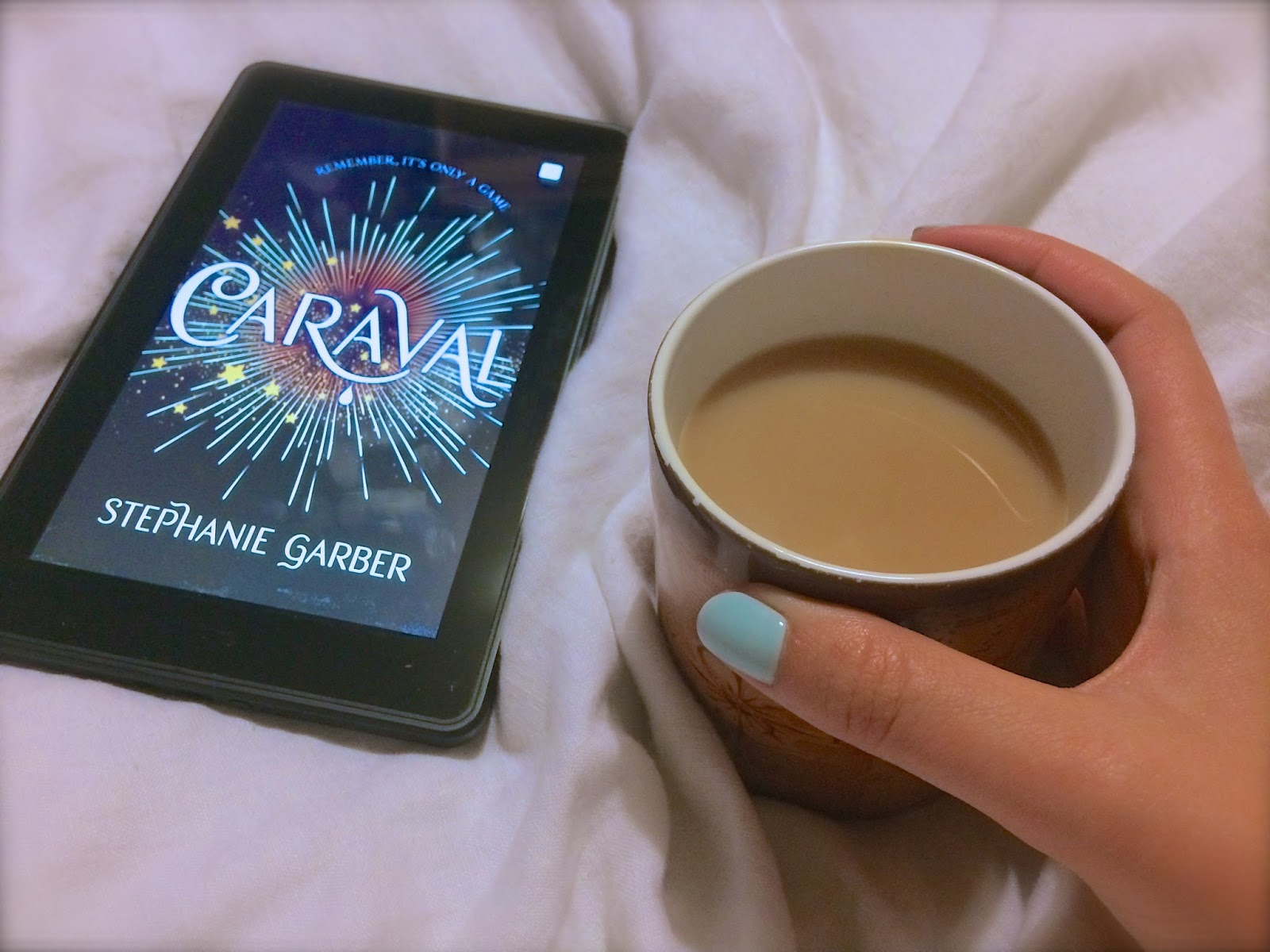 Caraval on Kindle Fire and cup of tea