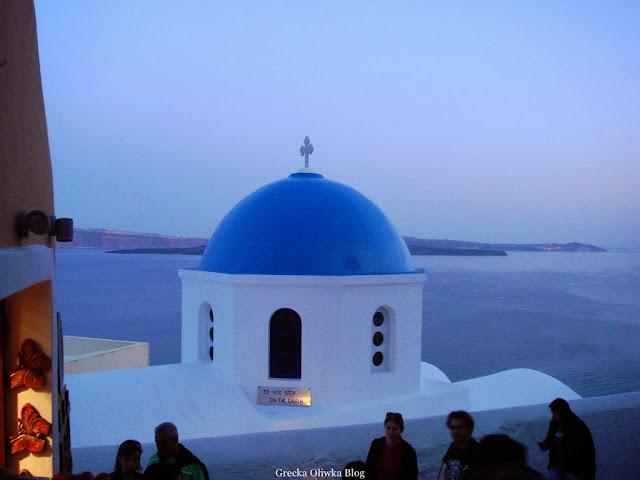 biały grecki kościołek z niebiską kopułą na tle egejskiego morza Fira Santorini Grecja