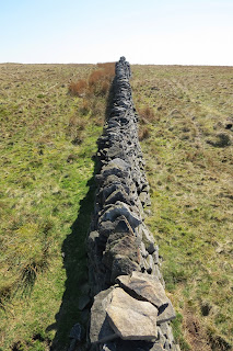 A picture looking along the top of a dry stone wall as it stretches into the distance.