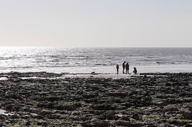 A rocky beach with a family silhouetted near the sea