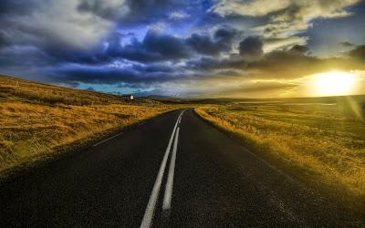 Carretera con sol de fondo y nubes moradas