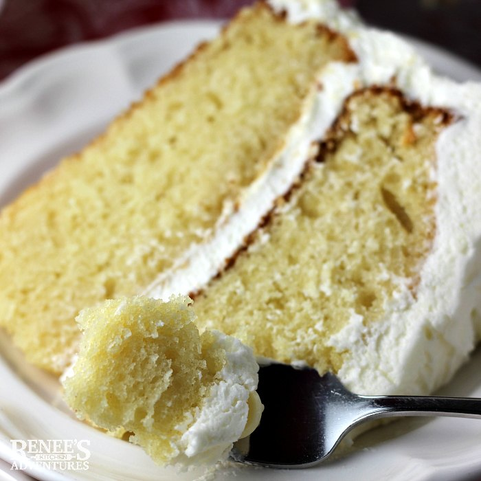 White Chocolate Cake by Renee's Kitchen Adventures slice of cake on a white plate with a bite on a fork