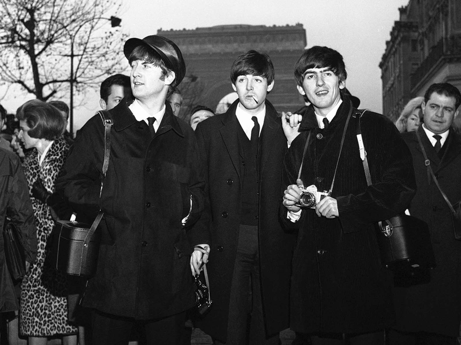 Sightseeing in Paris, on January 15, 1964, the day before their opening at the Olympia Theatre in Paris, three of Britain's four Beatles pause for a look around on the Champs Elysees. From left John Lennon, Paul McCartney and George Harrison. In the background is the Arc de Triomphe.