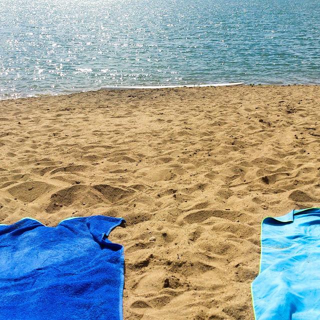 Gyoroki homokos strand két kék törölközővel