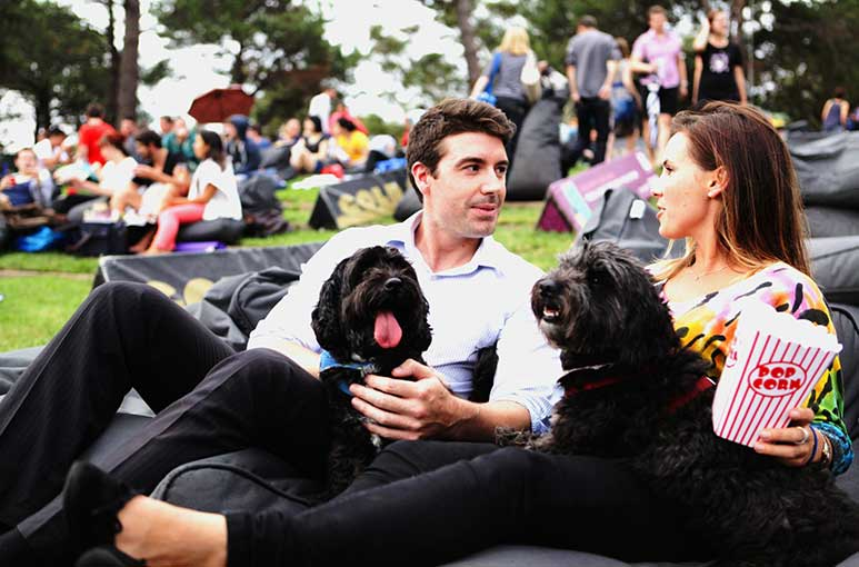 Couple with two black dogs at the Moonlight Cinema Doggie Nights
