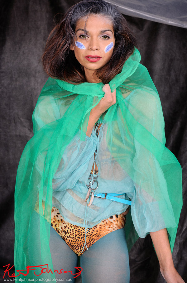 Sage Godrei, magazine style actors portrait; studio photography, black background, Sage in fantasy outfit, mid shot.