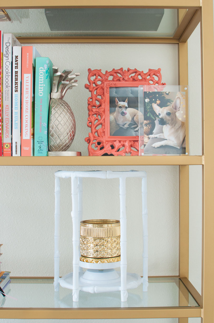 Books, photos and chinoiserie decor adorn a chic bookcase etagere in a black, white and gold living room.