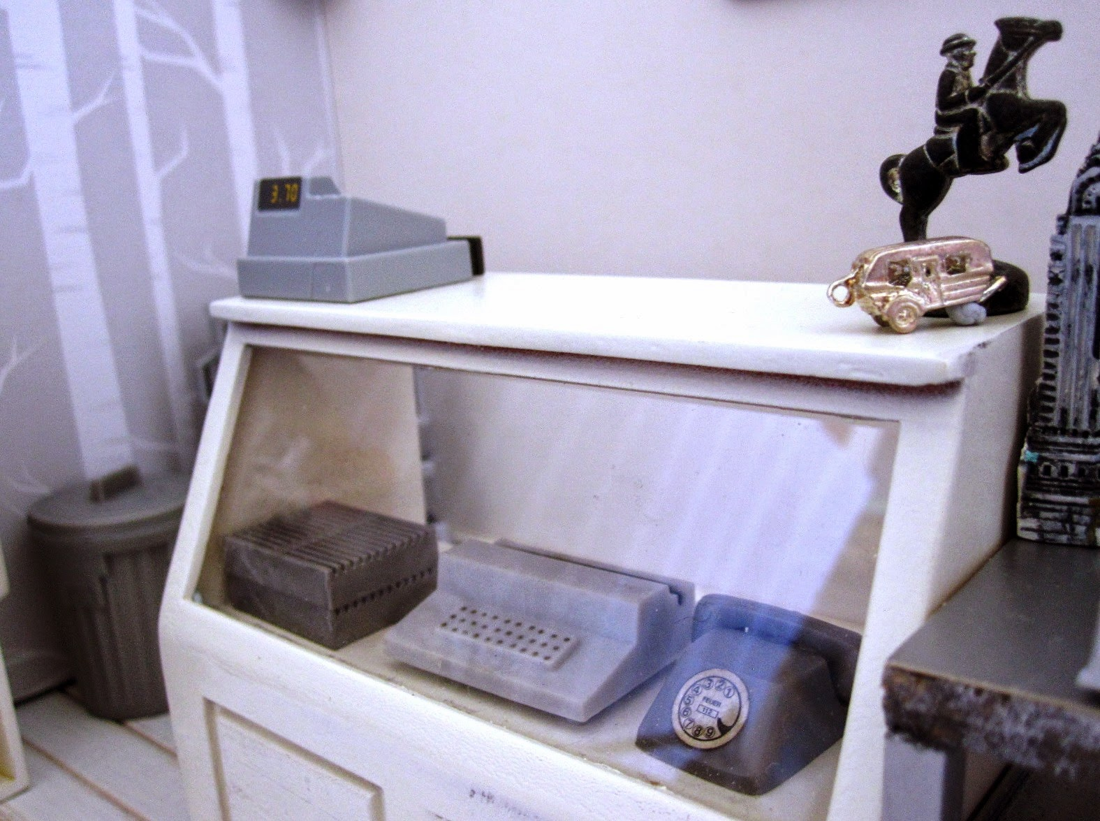 Counter of a modern dolls' house miniature homeware shop in grey and white. On the counter is a cash register and two silver statues. On display under the counter is a vintage grey typewriter and a vintage grey telephone.