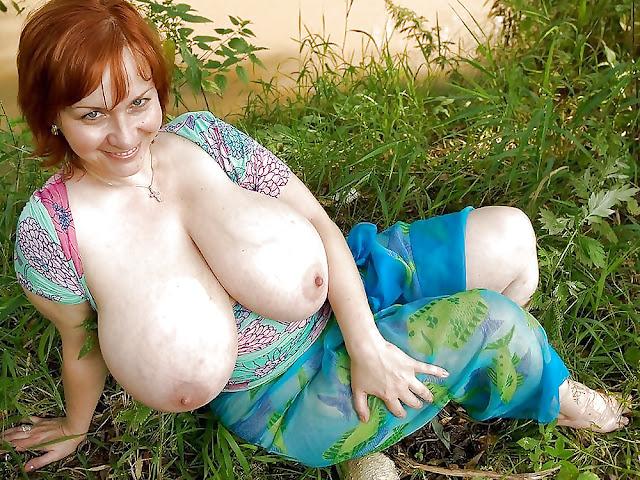 rothaarige Frau zeigt ihre Monstertitten in der Natur