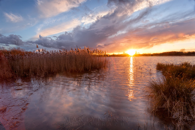 Evening clouds above a beautiful sunset at Ouse Fen Nature Reserve lake