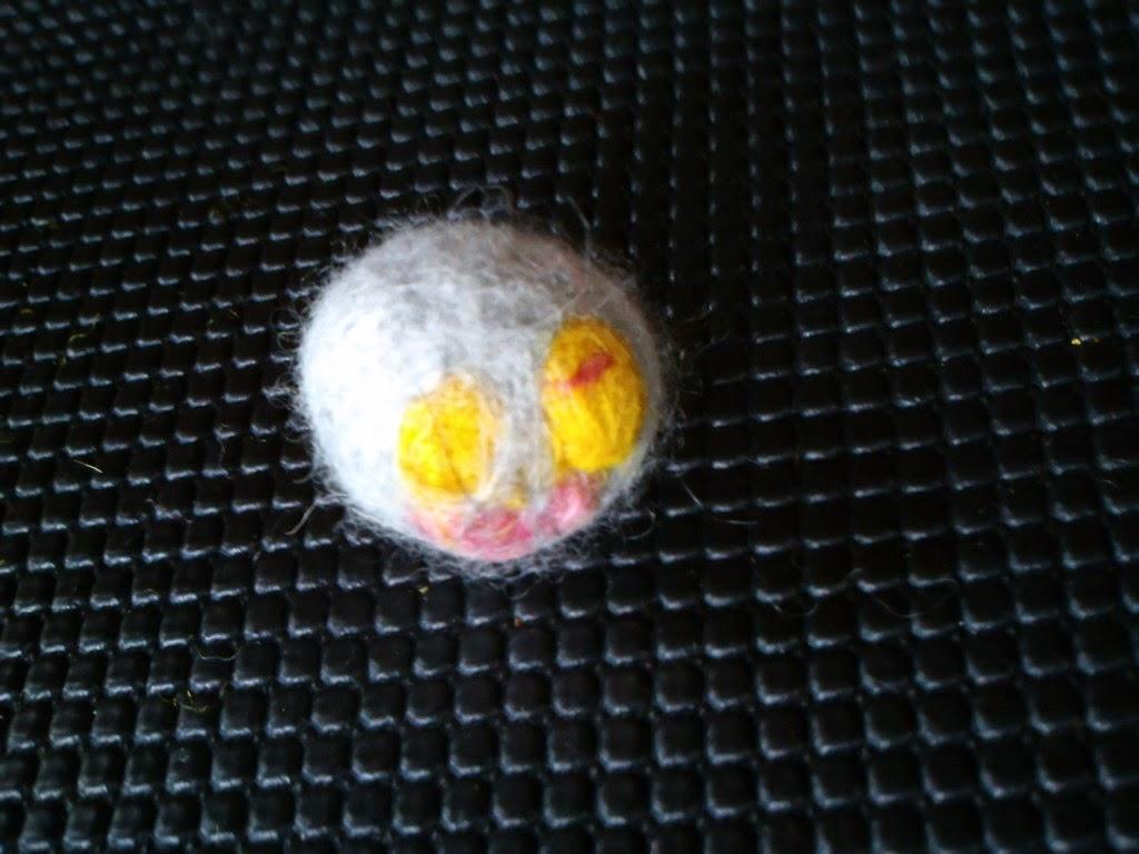 bola feita de lã com duas marcas amarela