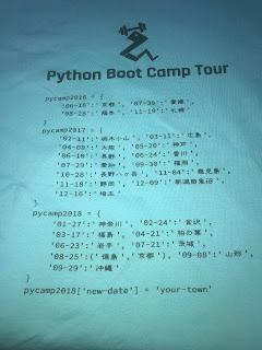 背中は過去の開催日と開催地をPythonの辞書型で表しています(この写真は後日撮影)