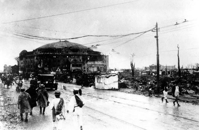 As pessoas andam na área devastada de Yuoguku, em Tóquio, Japão, após o terremoto que ocorreu em 1º de setembro de 1923. No fundo, está o edifício abobadado de cúpulas Kokugikan, arena de luta nacional de sumô, no distrito de Ryoguku.
