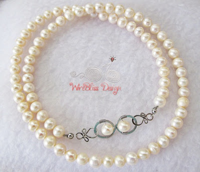 Stringed pearl necklace with wire wrap infinity clasp by WireBliss