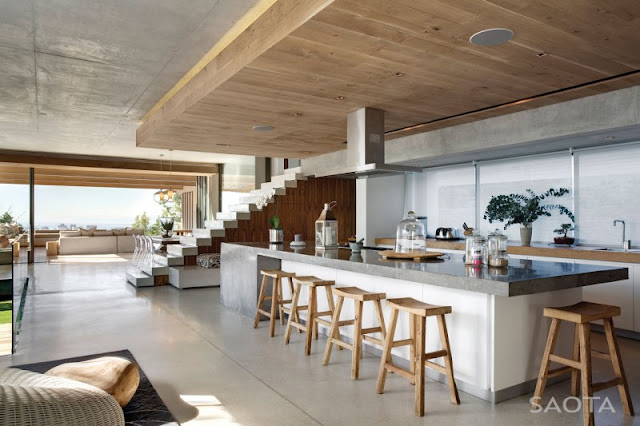 Photo of huge kitchen island with five wooden bar chairs