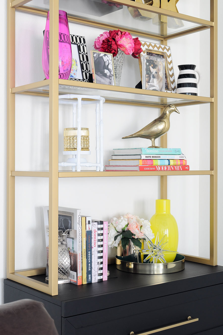 Spring decor ideas for a bookshelf, bookcase or etagere. This bookcase looks so glam, bold and colorful.