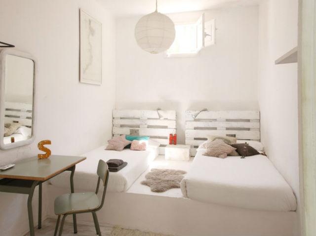 dormitorio con pared hecha con madera de palets y escritorio de escuela