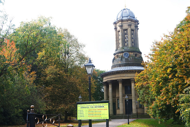 a church with pillars and a metal domed roof sits in a park surrounded by autumn trees