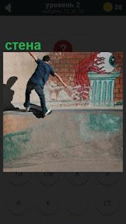 мальчик около стены катается на скейтборде