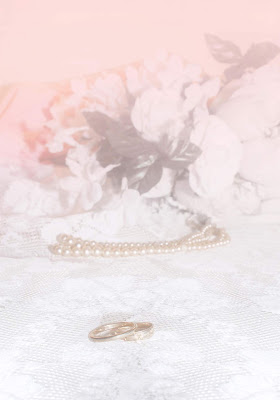 A wedding background or printage paper with blurred floral bouquet in the background, a lace clothing holding vintage pearls and two gold wedding rings.