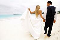 Balayı tatilinde deniz kenarında el ele tutuşmuş gelin ve damat