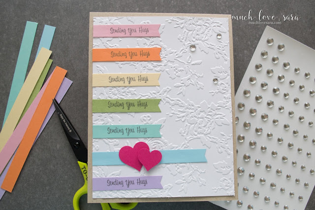 This card is perfect to send to someone that need a little reminder that they are thought of and loved.  The pastel rainbow banners stamped with the Text Happy stamp, share written hugs, along with a little love from the punched hearts.  Created with Fun Stampers Journey stamps, paper, and products.