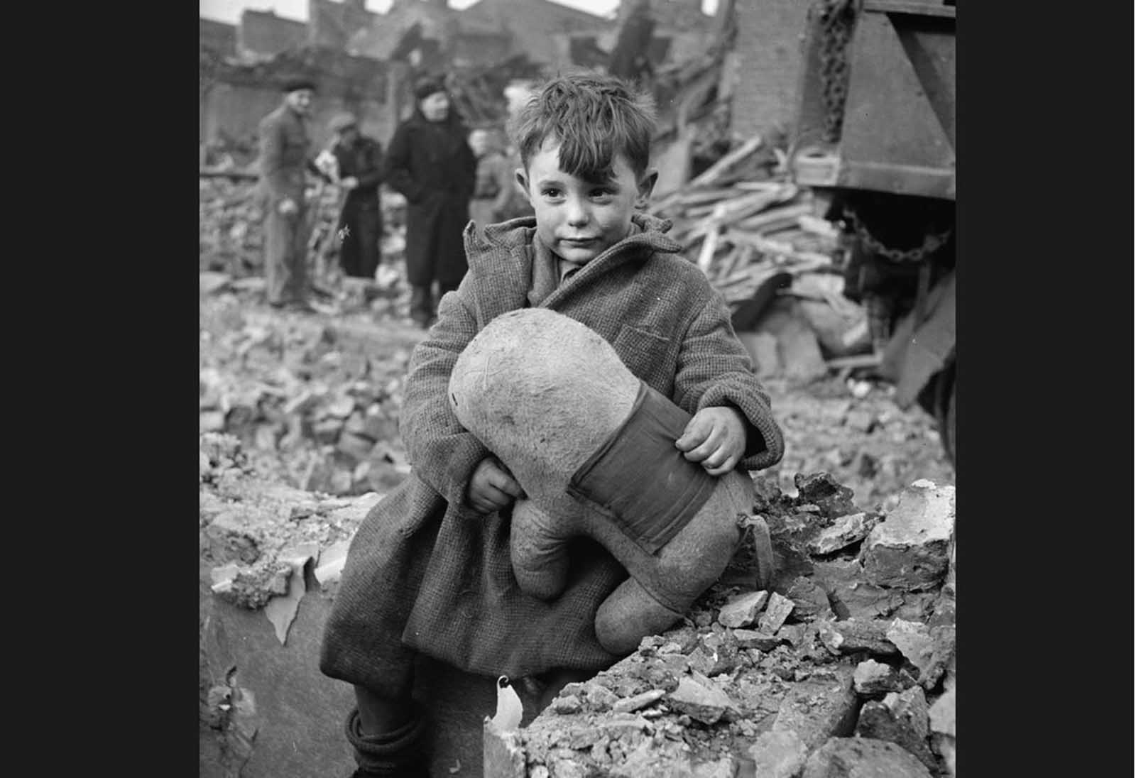 An abandoned boy, holding a stuffed toy animal amid ruins following a German aerial bombing of London in 1940.