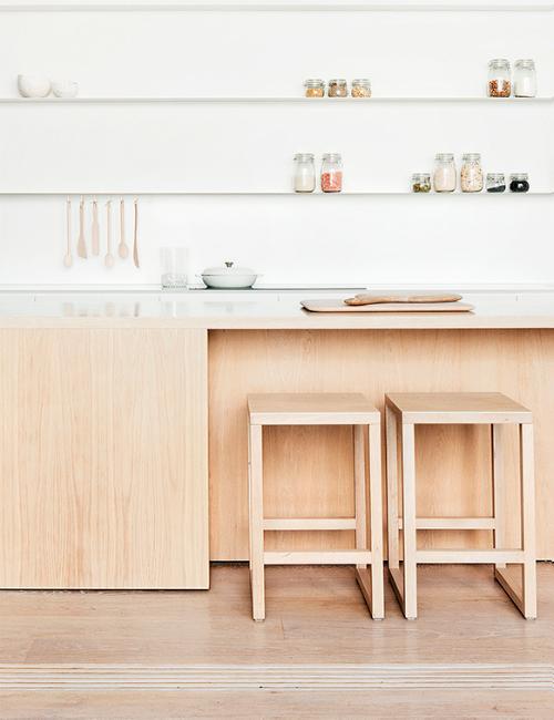 Küche mit einer Arbeitszeile und Hockern aus hellem Holz  gestaltet von studiofour.