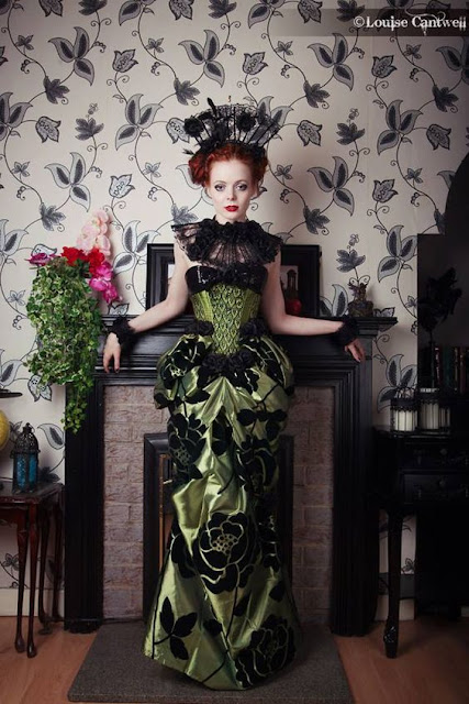 Woman wearing a Neo-Victorian dress to a masquerade ball. Green and black skirt and bodice, with floral print, lace collar, lace wrist cuffs, feather fascinator. Evening Gown can be worn to a Steampunk ball.